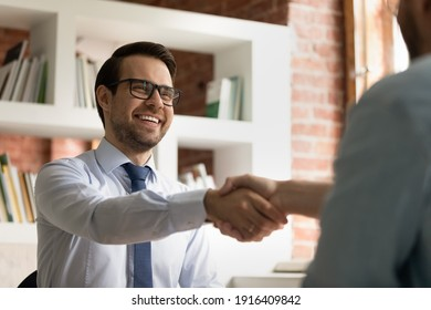 Smiling young Caucasian businessman shake hand of partner or colleague close deal after successful meeting in office. Happy male CEO or employee handshake get acquainted greet with business client.