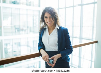 smiling young Caucasian businesswoman holding mobile phone in office