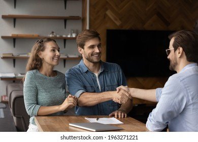 Smiling young Caucasian couple shake hand with male realtor or broker at office meeting. Happy man and woman clients handshake close deal make agreement with real estate agent. Rental, rent concept.