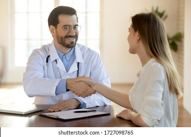 Smiling young Caucasian male doctor or GP in white medical uniform handshake female patient sign health insurance agreement, happy man physician shake hand of client get acquainted at consultation