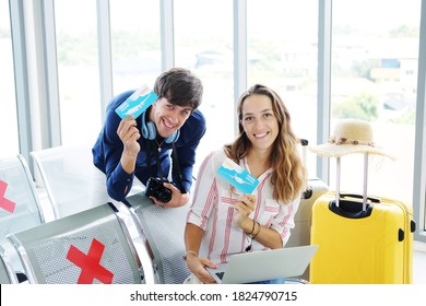 Smiling Young Caucasian traveler couple love is holding travel voucher of the airline for honeymoon trip on vacation together in the airport.
