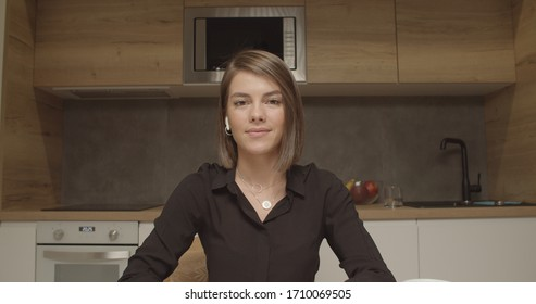 Smiling young caucasian woman blogger vlogger influencer sit at home kitchen speaking looking at camera talking make video chat, conference call record lifestyle blog vlog, webcam view