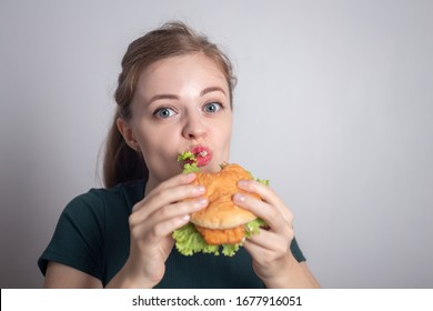Smiling young Caucasian woman girl holding eating chicken burger