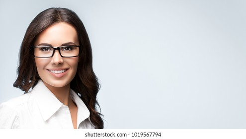 Smiling young cheerful brunette businesswoman in glasses, over grey background, with copyspace area for slogan or text message. Success in business concept studio shot.