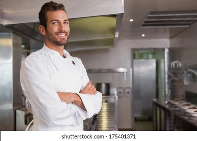 Smiling young chef standing with arms crossed in a commercial kitchen