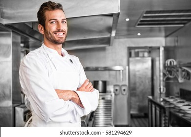 Smiling young chef standing with arms crossed in professional kitchen