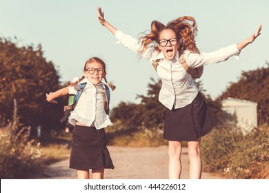 Smiling young  children in a  uniform jumping on the road in the park at the day time. Concept of the girls are ready to go to school.