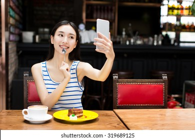 smiling young chinese woman holding phone and coffee self-timer