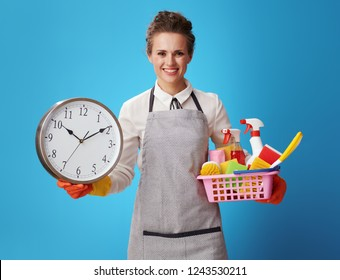 smiling young cleaning woman in apron with a basket with detergents and brushes showing clock on blue background. Accuracy, quality, reliability, individual approach from professional cleaners