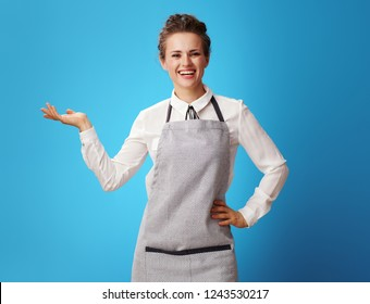 smiling young cleaning woman in apron presenting something on empty palm isolated on blue. Cleaning woman shows bonuses of work with professional cleaning service