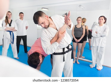 Smiling young coach showing a new submission hold to adults in a taekwondo class