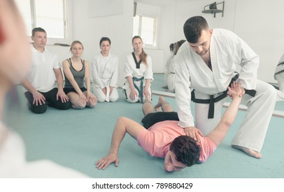 Smiling young coach showing new submission hold to adults at a taekwondo class
