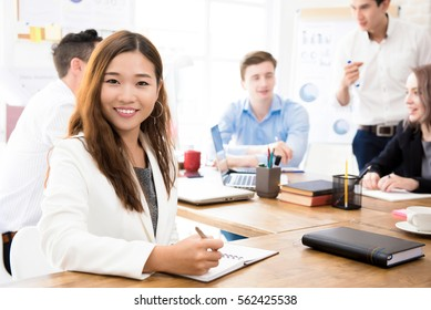 Smiling young confident Asian businesswoman at the office with her mixed race colleagues in background
