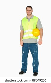 Smiling young construction worker carrying his helmet under his arm against a white background