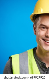Smiling young construction worker in hard hat, vertical crop