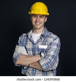 smiling young construction worker on a black background