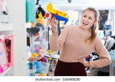 smiling young consumer with children's plastic toys in the kids store