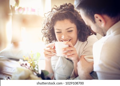 Smiling young couple in bed drinking coffee and looking each other. Close up.
