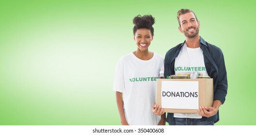 Smiling young couple with clothes donation against green vignette