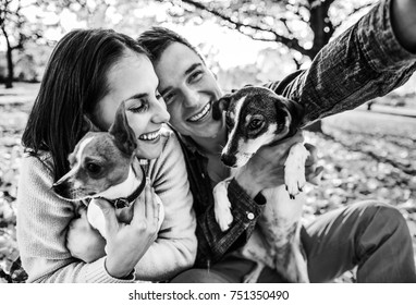 Smiling young couple with dogs outdoors in autumn park making selfie