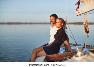 Smiling young couple enjoying the ocean view while sitting together on the deck of their boat on a sunny afternoon