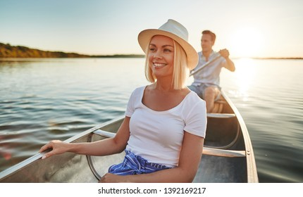 Smiling young couple enjoying a summer day paddling their canoe on a lake in the late afternoon