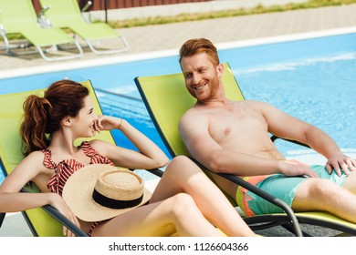smiling young couple flirting while relaxing on sun loungers in front of swimming pool
