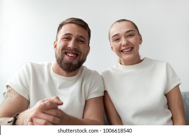 Smiling young couple with happy faces looking at web camera, man and woman making videocall to distance friend by skype, funny vloggers recording videoblog or video message, webcam view portrait