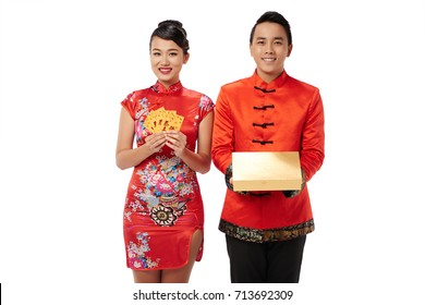 Smiling young couple holding greeting cards and present for Tet celebration
