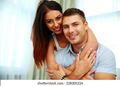 Smiling young couple hugging at home