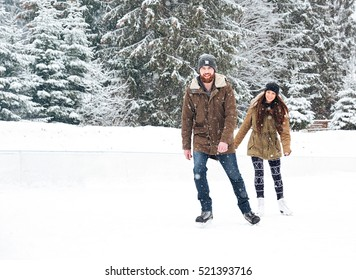 Smiling young couple ice skating outdoors with snow on background