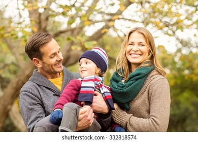 Smiling young couple with little boy posing on an autumns day