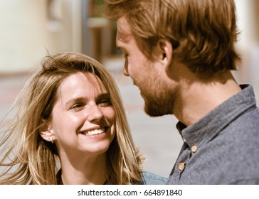 Smiling young couple looking at each other tenderly as love concept