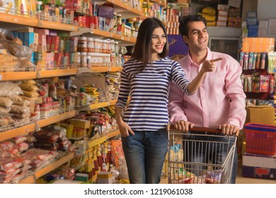 Smiling young couple looking at products at a super market holding a shopping cart while purchasing groceries.