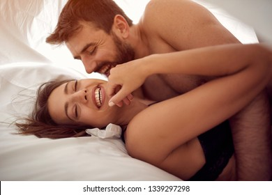 Smiling young couple lying and hugging in bed at home