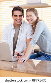 Smiling young couple with notebook in the kitchen