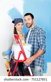 Smiling Young Couple with Paint Bucket, Roller and Ladder