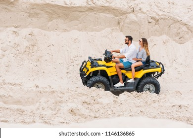 smiling young couple riding all-terrain vehicle in desert