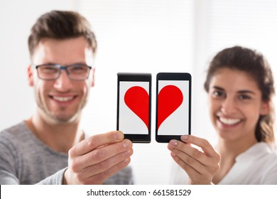 Smiling Young Couple Showing The Heart Shape By Joining Their Cell Phone