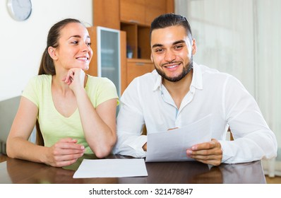 Smiling young couple signing financial documents at the table