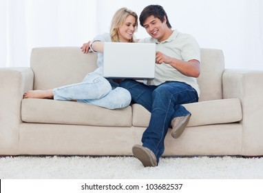 A smiling young couple are sitting down on a couch looking at a laptop