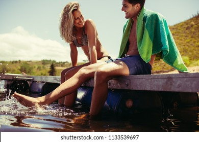 Smiling young couple sitting on the pier dangling legs in water. Young man and woman relaxing on a jetty at the lake. Both in swimwear.