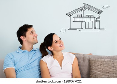 Smiling Young Couple Sitting On Sofa Thinking Of Getting Their New House