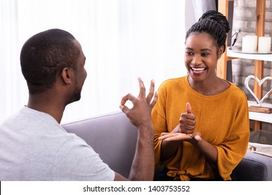 Smiling Young Couple Sitting On Sofa Communicating With Sign Languages