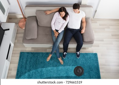 Smiling Young Couple Sitting On Sofa Watching Cleaning Robot