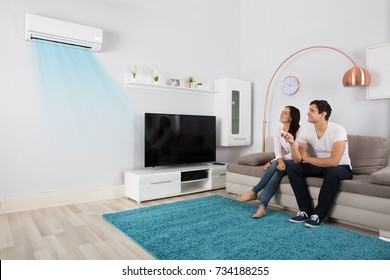 Smiling Young Couple Sitting On Sofa Using Air Conditioner
