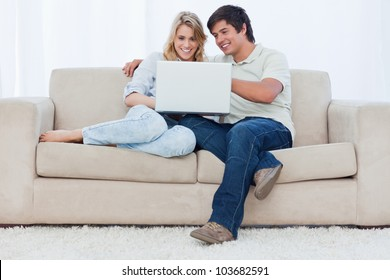 A smiling young couple are sitting together on a couch looking at a laptop