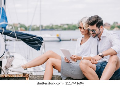 smiling young couple in sunglasses sitting and using digital tablet near yacht
