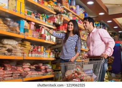 Smiling young couple at a super market with a shopping cart purchasing groceries.