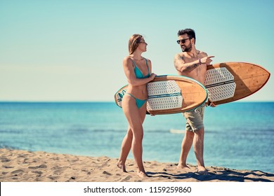 Smiling young couple of surfers walking on the beach Summer outdoor lifestyle.